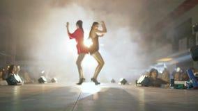 La presentación de la ropa de diseñador, los modelos zanquilargos en zapatos de tacón alto va a lo largo del podio iluminado por  almacen de metraje de vídeo