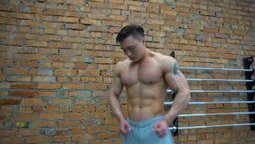 La presentación muscular y apta del culturista demuestra los músculos de la base almacen de metraje de vídeo