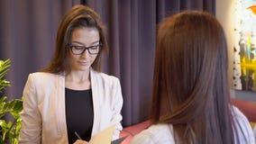 La presentadora de sexo femenino acoge con satisfacción al cliente mientras que se coloca en restaurante almacen de video