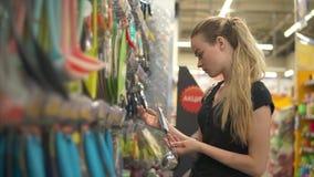La presentadora joven está examinando las cucharones en un pasillo en un hipermercado almacen de video