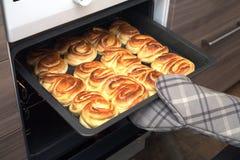La presentadora toma las tortas crujientes acabadas del mitón del horno de la cocina que se sostiene con la manopla de la cocina  Imágenes de archivo libres de regalías