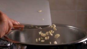 La presentadora vierte el ajo cortado en trozos pequeños en el agua almacen de metraje de vídeo