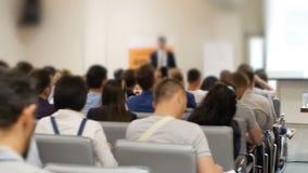 La presentazione di affari sullo schermo proiettivo su una conferenza e gli ascoltatori appoggiano stock footage