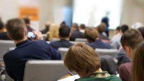 La presentazione di affari sullo schermo proiettivo su una conferenza e gli ascoltatori appoggiano archivi video