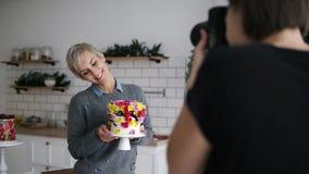 La presentazione femminile del confettiere decorata con i fiori agglutina nella sua cucina Processo di photoshooting Metraggio da video d archivio