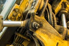 La presión amarilla sucia del sistema hydráulico de la niveladora del excavador parte Fotos de archivo libres de regalías