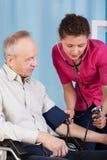 La pression de la patiente de mesure d'infirmière Photos libres de droits