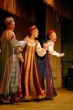La prestazione del gruppo di folclore mostra, ruota dell'insieme in costumi russi tradizionali Immagine Stock