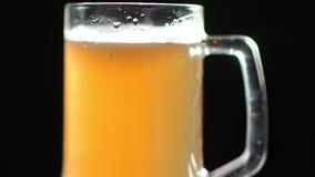 La prestazione di bella birra fresca con le bolle e di schiuma in tazza di vetro ha riguardato le gocce di acqua archivi video