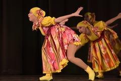 La prestazione teatrale dei bambini del gruppo di ballo in costumi nazionali Fotografie Stock