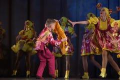 La prestazione teatrale dei bambini del gruppo di ballo in costumi nazionali Fotografia Stock