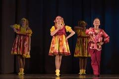 La prestazione teatrale dei bambini del gruppo di ballo in costumi nazionali Immagini Stock Libere da Diritti