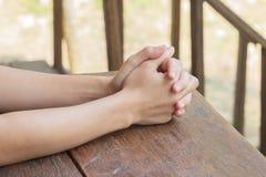 La prière de femme prient sur un brun en bois de table dehors Mains, espoir longing Images stock