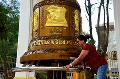 La prière et le rite thaïlandais de personnes de dame âgée tournent et tournent la grande cloche Image libre de droits