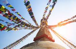 La prière marque le vol contre le soleil du Boudhanath Stupa Image libre de droits
