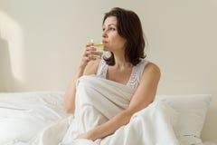 La prima bevanda di mattina di una donna matura adulta è antiossidante - innaffi con un limone, sedentesi a letto fotografia stock