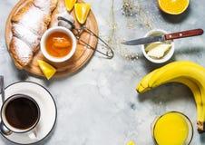 La prima colazione è servito con caffè, succo d'arancia, i croissant ed i frutti su fondo concreto fotografia stock libera da diritti