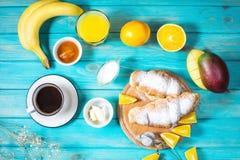 La prima colazione è servito con caffè, succo d'arancia, i croissant ed i frutti su fondo di legno blu fotografia stock