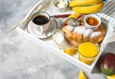 La prima colazione è servito con caffè, succo d'arancia, i croissant ed i frutti sul vassoio bianco immagini stock