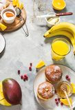 La prima colazione è servito con succo d'arancia, la ciambella ed i frutti su fondo concreto fotografia stock