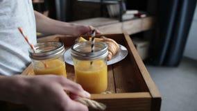 La prima colazione deliziosa sul vassoio di legno è servito dall'uomo stock footage