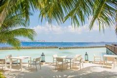 La prima colazione ha installato con le tavole e le sedie alla spiaggia tropicale Fotografie Stock