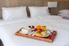 La prima colazione ha messo nel servizio di legno del vassoio sul letto Fotografie Stock Libere da Diritti