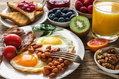 La prima colazione inglese è servito con l'uovo fritto, i fagioli, i pomodori, il succo d'arancia, il bacon ed il pane tostato co fotografia stock
