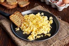 La prima colazione rustica casalinga ha rimescolato le uova sulla pentola con pane tostato arrostito Fotografia Stock