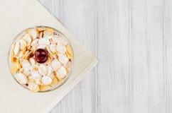 La prima colazione sana con i fiocchi di mais dorati, le ciliege mature, lo zucchero in polvere sul punto di vista superiore del  Fotografie Stock