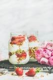 La prima colazione sana della molla della disintossicazione stona con i fiori rosa di raninkulus fotografia stock