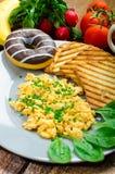 La prima colazione sana ha rimescolato le uova con la erba cipollina, pane tostato di panini Fotografia Stock