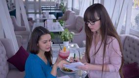 La prima colazione sana, la ragazza con il taccuino e la penna a disposizione annota il piano di dieta insieme all'amica che si s video d archivio