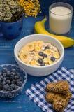 La prima colazione utile e molto saporita, farina d'avena si sfalda, mirtilli, le banane, il latte, il kozinaki delle pesche, dol Fotografia Stock