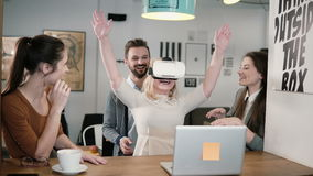 La prima esperienza con gruppo di vetro di realtà virtuale il giovane sostiene la giovane bella ragazza bionda in ufficio startup immagine stock libera da diritti
