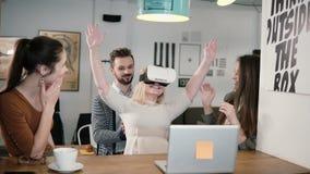La prima esperienza con gruppo di vetro di realtà virtuale il giovane sostiene la giovane bella ragazza bionda in ufficio startup fotografie stock