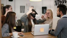La prima esperienza con gruppo di vetro di realtà virtuale il giovane sostiene la giovane bella ragazza castana in ufficio startu immagine stock