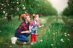 La primavera de la mujer del bebé cultiva un huerto y mujer, dientes de león Fotografía de archivo