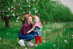 La primavera de la mujer del bebé cultiva un huerto y mujer, dientes de león Fotografía de archivo libre de regalías