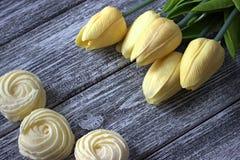 La primavera fiorisce i tulipani con le caramelle gommosa e molle dello zefiro su fondo di legno grigio Il giorno della donna 8 m Fotografia Stock