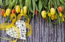 La primavera florece el ramo de tulipanes y de narcisos amarillos y rojos en un fondo gris con el adorno de la pared y ladrillo c Imagenes de archivo