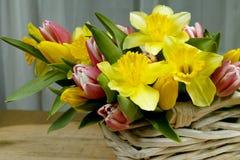 La primavera multicolora del ramo florece con la cesta de mimbre en de madera Fotos de archivo libres de regalías