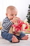 La primera Navidad: bebé descalzo que desempaqueta un presente rojo - l lindo Imagenes de archivo