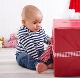 La primera Navidad: bebé que desempaqueta un presente rojo con un checke rojo Imagenes de archivo