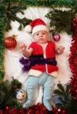 La primera Navidad del bebé Pequeño bebé hermoso en el sombrero de Papá Noel en Chr Imágenes de archivo libres de regalías