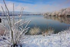 La primera nieve en un lago de la montaña fotos de archivo