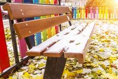 La primera nieve miente en un banco de madera con el respaldo y en las hojas amarillas y verdes, concepto de la soledad fotografía de archivo libre de regalías