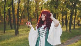 La princesse féerique merveilleuse regarde la pomme magique dans sa main, grand modèle dodu avec de longs cheveux onduleux rouges clips vidéos