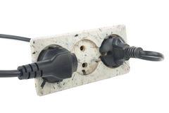 La prise électrique triple sur le mur blanc avec deux a branché des câbles Photo stock