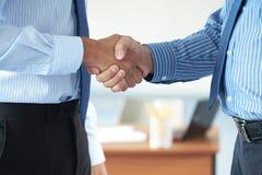La prise de contact, deux mains mâles les deux utilisent les chemises bleues Photographie stock libre de droits